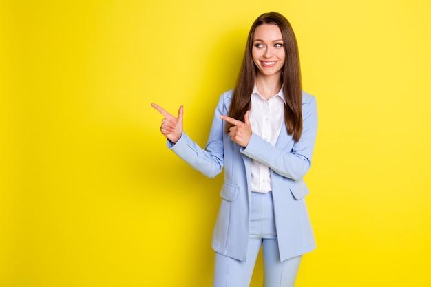 Photo d'une fille positive spécialiste du marketing pointer l'index copyspace démontrer les publicités de l'entreprise porter un pantalon blazer de style isolé sur fond de couleur brillante et brillante