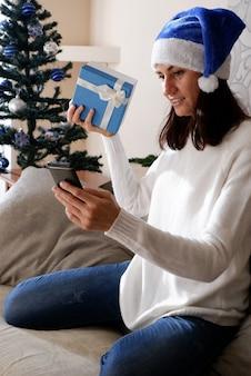 Photo d'une fille positive en train de taper une lettre sur un smartphone assis sur un canapé confortable dans une maison à l'intérieur avec noël