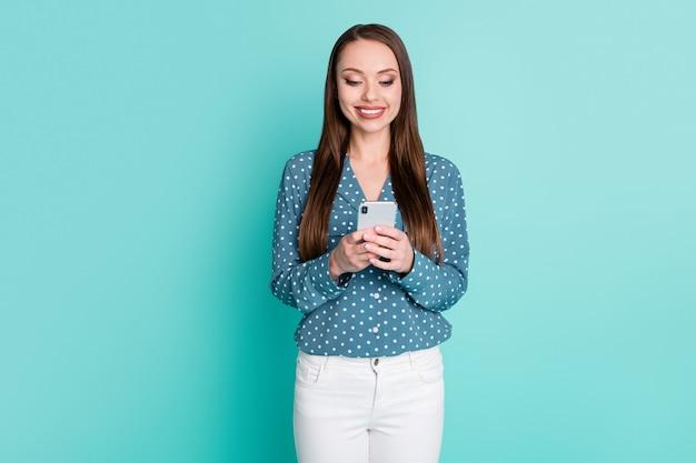 Photo d'une fille positive utilisant un téléphone intelligent pour partager des messages sur les réseaux sociaux isolés sur un fond de couleur sarcelle
