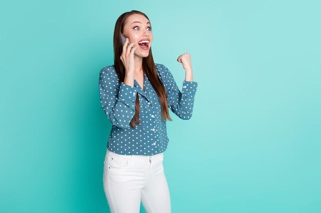 Photo d'une fille ravie parler sur smartphone lever les poings crier ouais isolé sur fond de couleur sarcelle