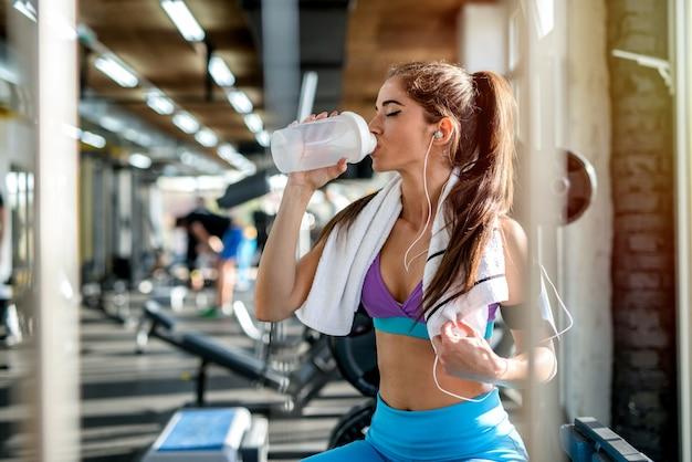Photo d'une fille sexy en forme assise dans une salle de sport et de l'eau potable. écouter la musique et se reposer après l'entraînement,