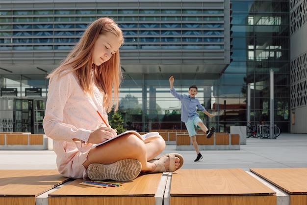 Photo d'une fille travaillant dans un cahier avec un crayon sur un banc dans un environnement éducatif informel dans la cour d'école...