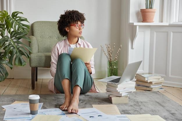 Photo d'une financière réfléchie, pieds nus, compare les prix dans des documents papier