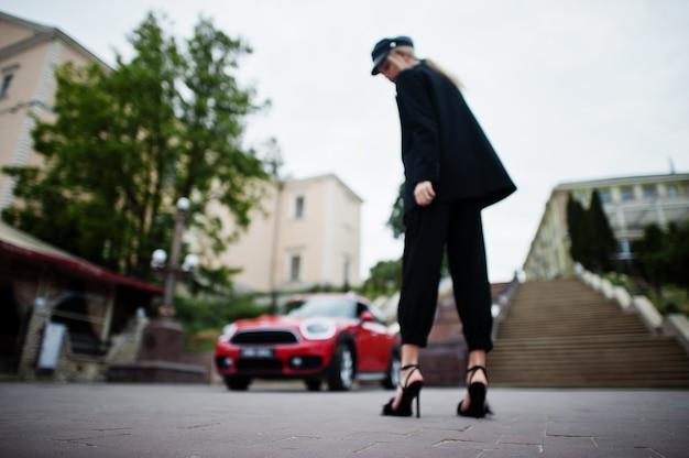 Photo floue du dos belle blonde sexy mannequin femme en casquette et en tout noir avec un maquillage lumineux près de la voiture de ville rouge.