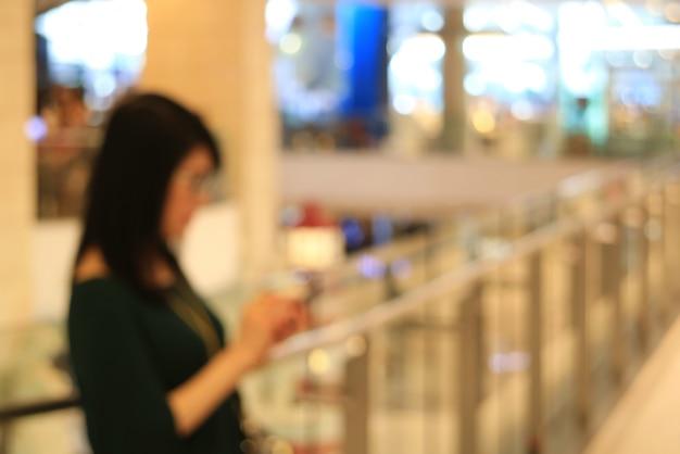 Photo floue d'une femme regardant un téléphone portable à la main dans le centre commercial de la mode