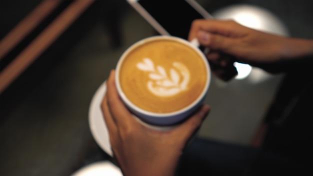 Photo floue d'une main de femme tenant l'art du latte sur le dessus dans des tasses à café au café