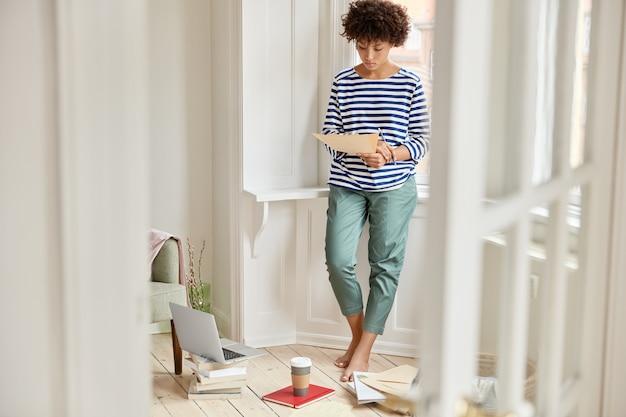 Photo fo femme responsable du marketing se tient dans une pièce spacieuse blanche, détient du papier