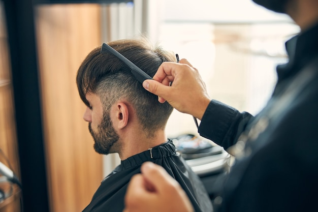 Photo focalisée sur le barbier debout en position semi et peignant les cheveux avant de couper