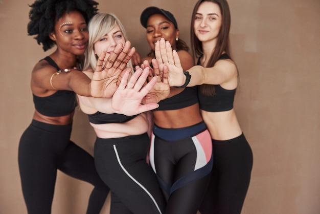Photo focalisée. groupe de femmes multiethniques debout contre l'espace brun