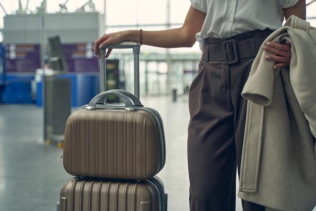 Photo focalisée sur une personne de sexe féminin debout près de ses bagages et tenant un manteau à la main