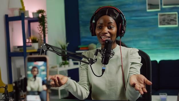 Photo focalisée sur un smartphone enregistrant une blogueuse africaine parlant en regardant la caméra pendant un podcast en ligne