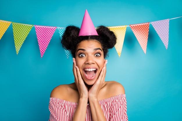 Photo de folle peau sombre dame bras pommettes surprise inattendue fête d'anniversaire porter une casquette de cône chemise rayée blanche rouge épaules nues drapeaux en pointillés colorés pendent sur un mur de couleur bleue