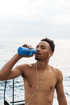 Photo d'un fort beau jeune homme sportif africain à l'extérieur à la plage mer eau potable écouter de la musique avec des écouteurs.