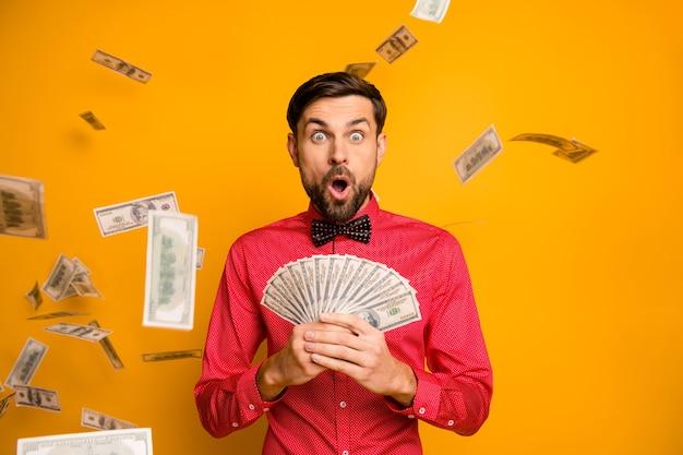 Photo de fou drôle mec tenir fan d'argent dollars billets de banque argent tombant bouche ouverte jackpot porter chemise rouge à la mode noeud papillon tenue