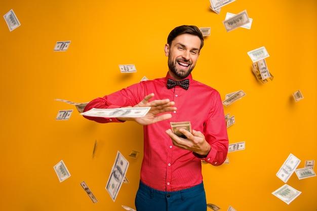 Photo de fou drôle mec tenir fan d'argent dollars gaspillage jackpot jetez les billets de banque argent tombant porter à la mode chemise rouge noeud papillon