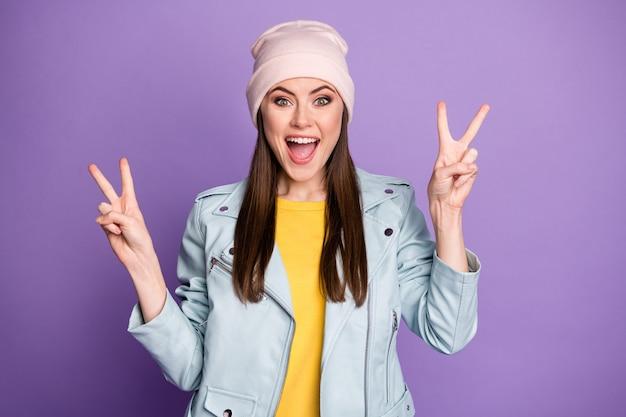 Photo de fou funky jolie dame bonne humeur montrant v-sign symboles mains personne joyeuse adolescent porter un chapeau décontracté bleu veste moderne isolé fond de couleur violet