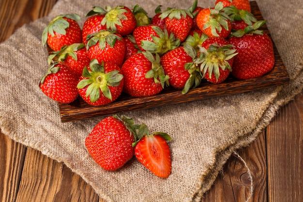 Photo de fraise mûre fraîche sur plaque en bois, gros plan de tissu toile