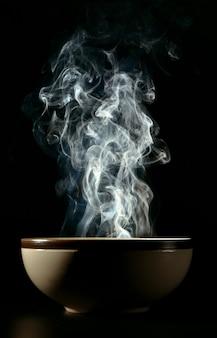 Photo de fumée s'élevant de la nourriture au-dessus de la tasse le concept de nourriture chaude.