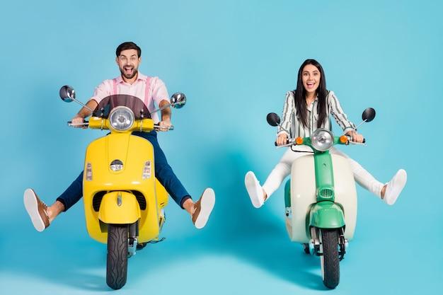Photo de funky deux personnes dame guy conduire rétro cyclomoteur voyageurs à grande vitesse évitant les embouteillages façon facile écartent les jambes près de flaque de vêtements de cérémonie vêtements isolés mur de couleur bleu