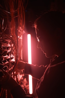 Photo futuriste d'un jeune ingénieur réseau travaillant avec un serveur en lumière rouge, se concentre sur le contour du profil