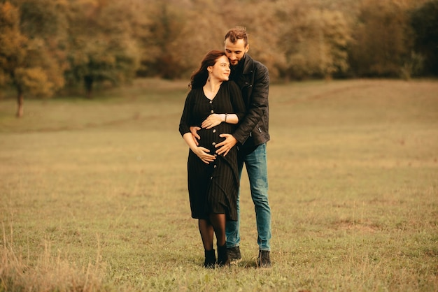 Photo de futurs parents heureux couple sur la promenade dans le parc, serrant par derrière
