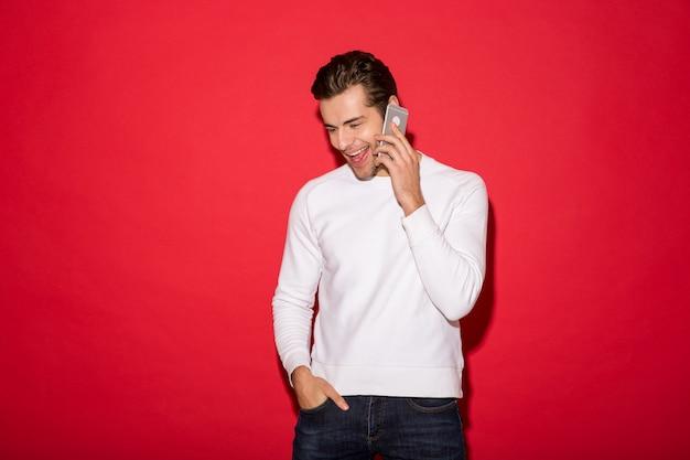 Photo de gai homme en pull parler par smartphone tout en regardant vers le bas et en tenant le bras dans la poche sur le mur rouge