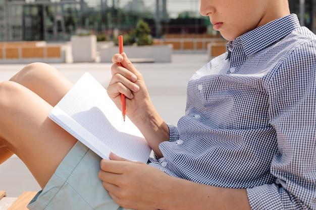 Photo d'un garçon travaillant dans un cahier avec un crayon sur un banc dans la cour d'école. environnement éducatif informel