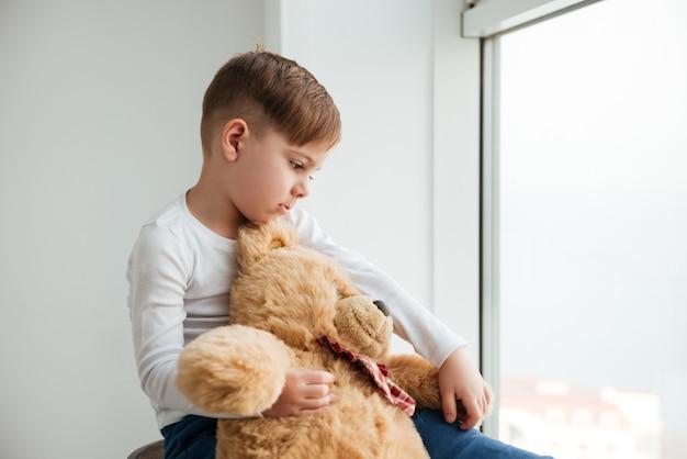 Photo d'un garçon triste près de la fenêtre avec un ours en peluche attendant les parents à la maison. regarder de côté.