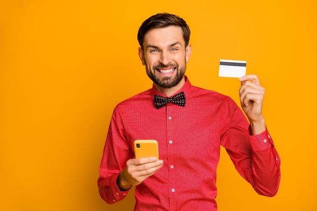 Photo de gars attrayant tenir le téléphone montrer nouvelle carte de crédit faire des achats en ligne moyen de paiement facile porter des vêtements à la mode chemise rouge noeud papillon