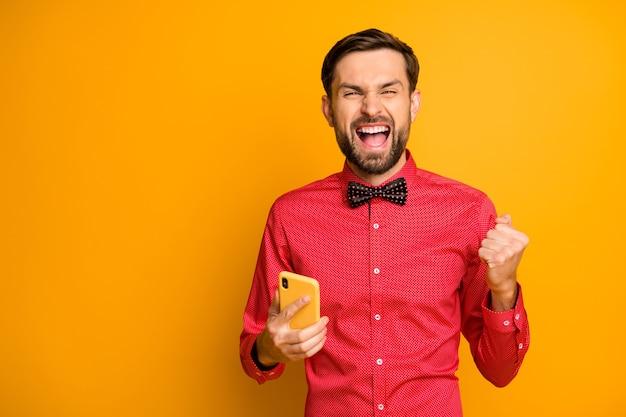 Photo de gars attrayant tenir téléphone travailleur de réseau social célébrant la croissance blog popularité tenues de soirée look tendance chemise rouge noeud papillon