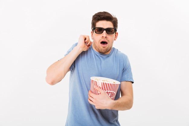 Photo de gars caucasien en t-shirt décontracté et lunettes 3d manger du pop-corn et regarder émotionnellement un film au cinéma, isolé sur mur blanc