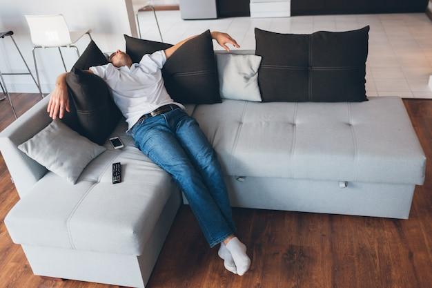 Photo d'un gars dans un sommeil profond ou une rêverie. assis ou allongé sur le canapé et tenez la main sur des oreillers noirs. dormez seul dans la chambre. homme fatigué et épuisé.