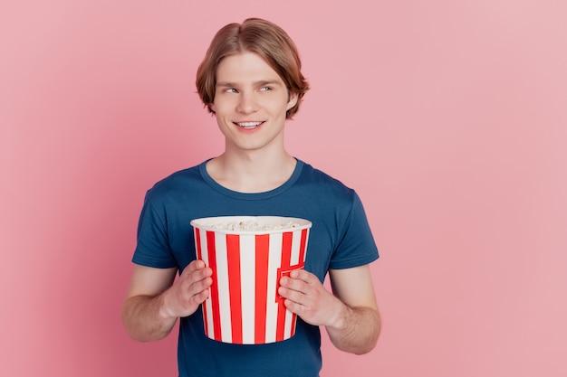 Photo d'un gars gai tenir une boîte de papier pop-corn heureux sourire positif regarder l'espace vide isolé sur fond de couleur rose