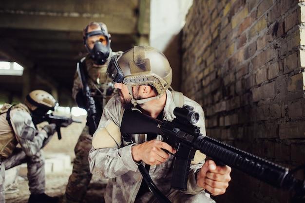 Une photo d'un gars à la recherche d'un objectif. il parcourt le pistolet à boucle. il est concentré. il y a deux personnes avec des fusils debout derrière eux. ils visent également.