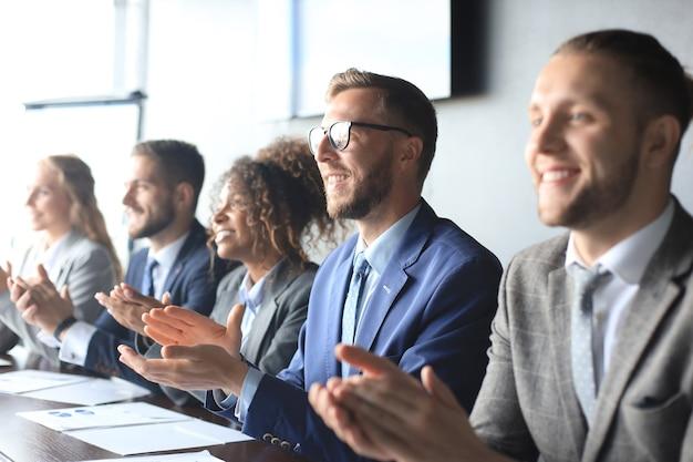 Photo de gens d'affaires heureux applaudissant à la conférence.