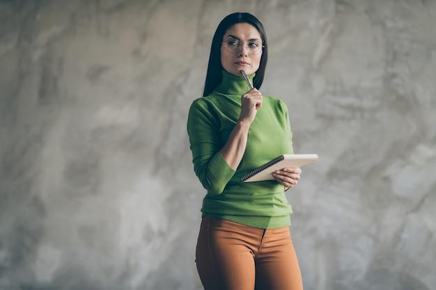 Photo de gens d'affaires réfléchis perplexes en pantalon pantalon orange portant des lunettes touchant le menton avec un stylo à la recherche dans l'espace vide mur gris isolé fond de couleur béton