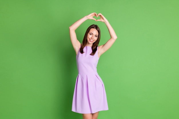 Photo de gentille adorable jeune fille modèle de dame montrer le signe du coeur deux mains au-dessus de la tête exprimer des sentiments d'amour aider la gentillesse soutenir porter une robe violette isolée fond de couleur vert pastel