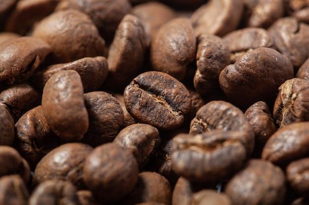 Photo de grains de café, fond uni, grains de café torréfiés, texture de grains de café torréfiés, haute qualité, gros plan