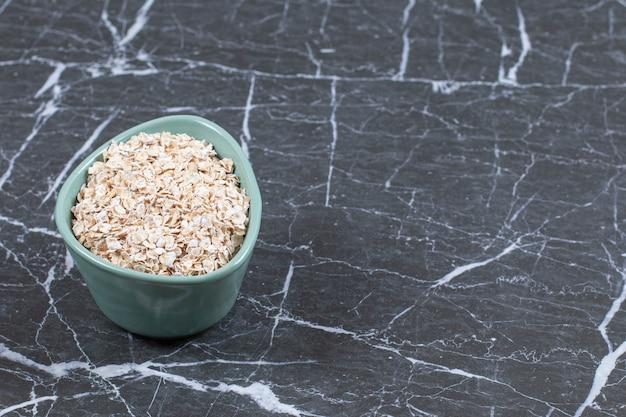 Photo grand angle d'avoine roulée ou de flocons d'avoine dans un bol en bois sur pierre.
