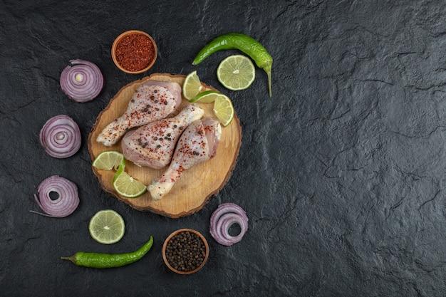 Photo grand angle de pilons de poulet cru et légumes sur planche de bois.