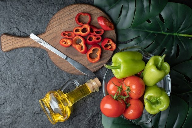 Photo grand angle de tomates mûres avec du poivre dans un bol et du poivron rouge tranché sur une planche de bois.