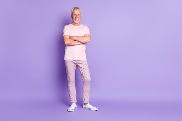 Photo de grand-père confiant les mains jointes portent un pantalon rose t-shirt baskets fond de couleur violet isolé