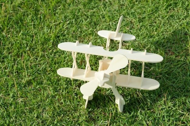 Photo en gros d'un avion de jouet en bois contre l'herbe