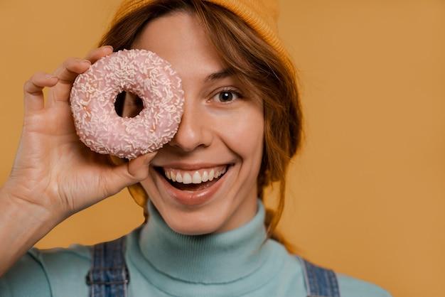 La photo en gros plan d'une agricultrice mignonne couvre son œil par un beignet et un sourire. porte une salopette en denim et un chapeau, fond de couleur marron isolé.