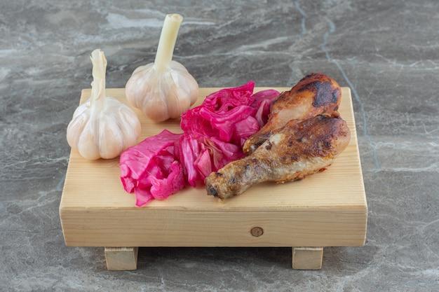 La photo en gros plan de l'ail et du chou en conserve avec des pilons de poulet grillés.