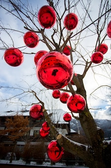 Photo gros plan d'un arbre sur la rue décorée de grosses boules rouges