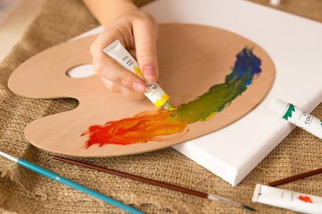 Photo gros plan d'un artiste pressant de la peinture à l'huile sur une palette à partir d'un tube