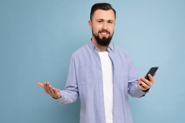 Photo en gros plan d'un beau calme demandant un beau jeune homme portant une tenue élégante et décontractée, isolé sur fond avec un espace vide tenant dans la main et utilisant la messagerie de téléphone portable sms loo