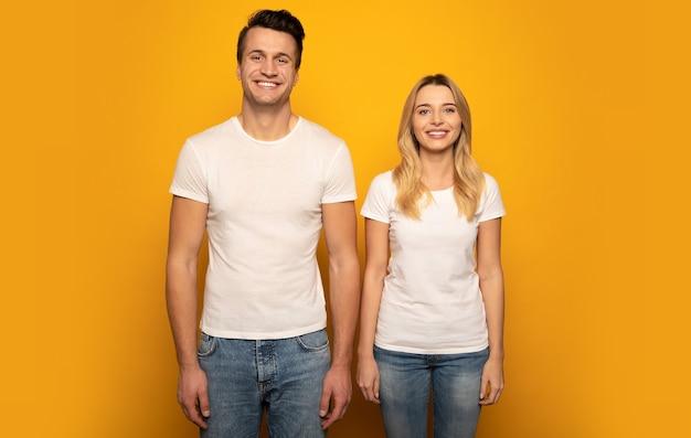 Photo en gros plan d'un beau couple, qui pose dans des t-shirts blancs sur fond jaune, les bras baissés, regardant dans la caméra et souriant.