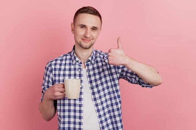 Photo gros plan de beau jeune homme heureux sourire positif tenir tasse café boisson show pouce vers le haut isolé fond pastel
